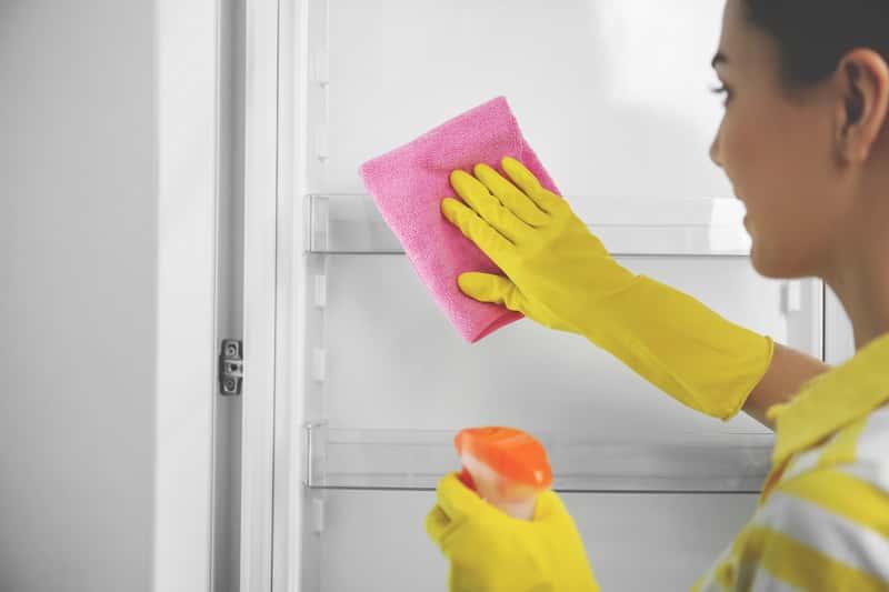 Kobieta podczas mycia lodówki