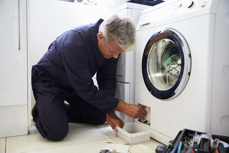 Mężczyzna podczas czyszczenia filtra pralki