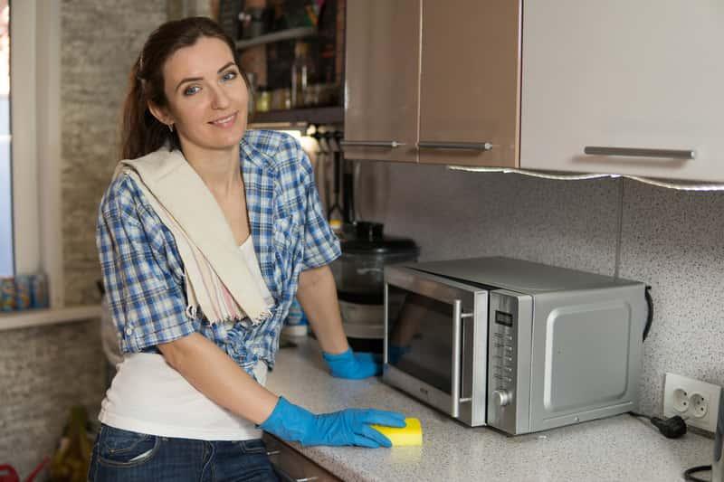 Kobieta podczas czyszczenia mikrofalówki