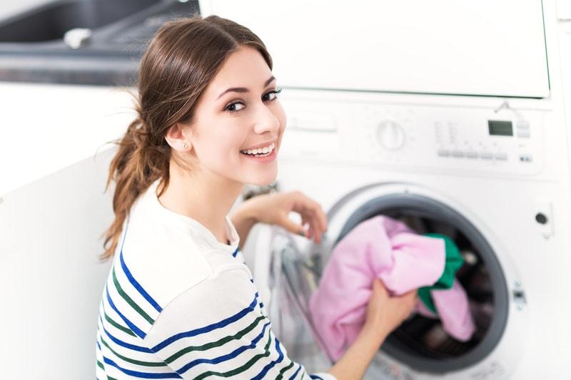 Uśmiechnięta kobieta przy pralce
