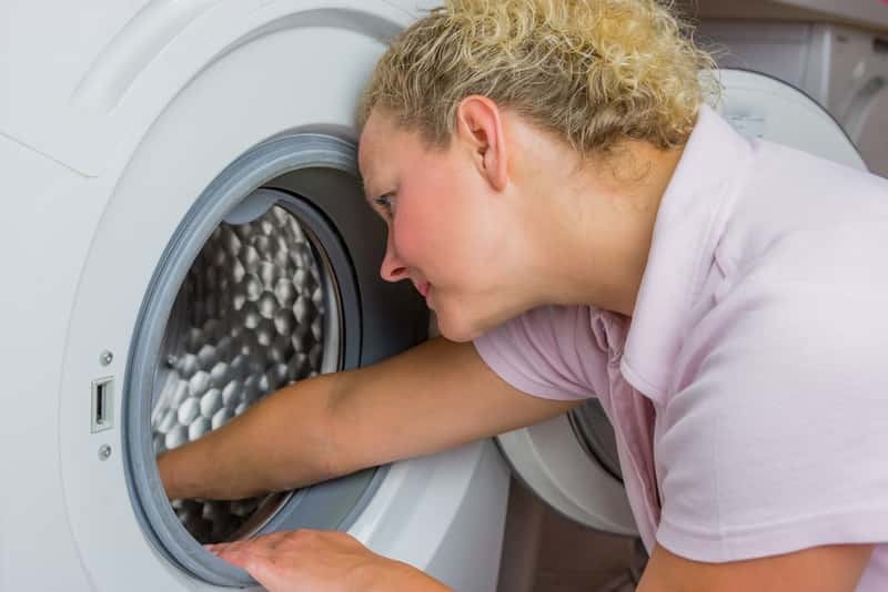 Kobieta podczas czyszczenia pralki