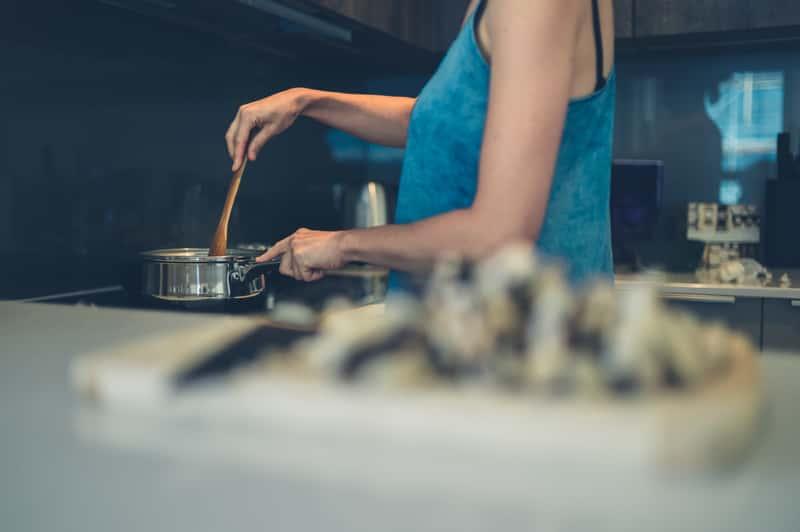 Kobieta gotująca obiad na płycie indukcyjnej Bosch. Kuchenka Bosch i jej polecane modele