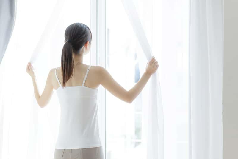 Kobieta odsłaniająca firanki w oknie
