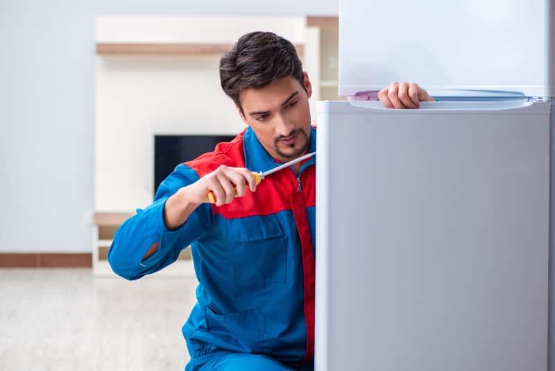 Wymiana uszczelki w lodówce przez mężczyznę, który wie, jak wymienić uszczelkę w lodówce