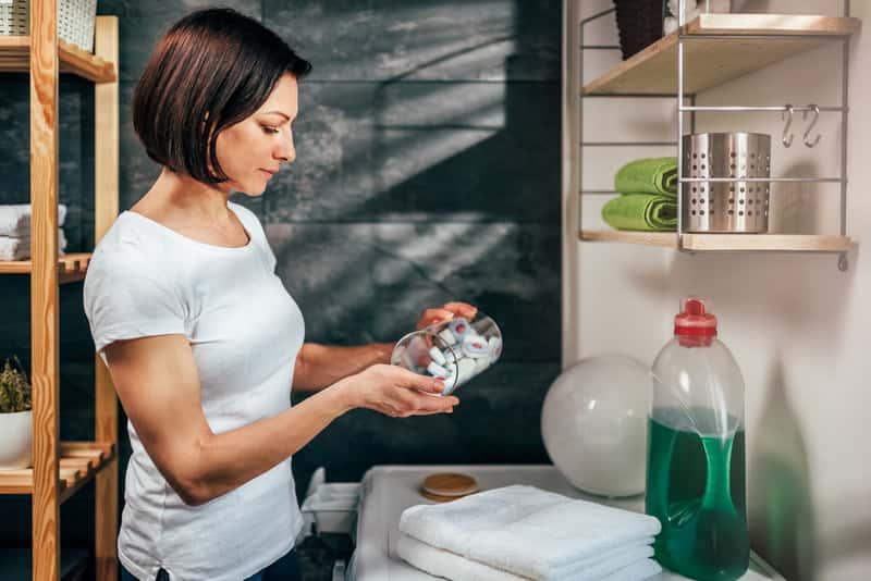 Kobieta używająca kapsułek do prania