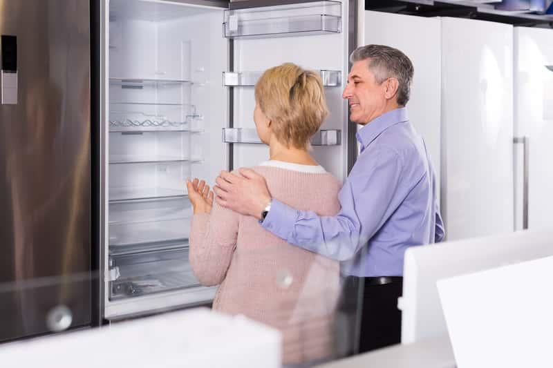 Małżeństwo oglądające lodówkę w sklepie