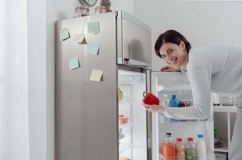 Kobieta sięgająca do lodówki Samsung, któreych warto poznać wady i zalety oraz opinie na ich temat przed planowanym zakupem