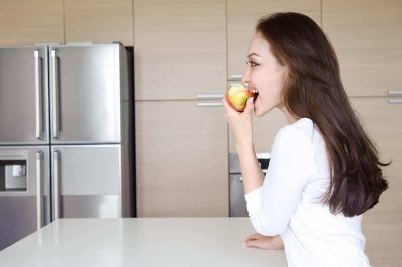 Kobieta gryząca jabłko obok amerykańskiej lodówki z podwójnymi drzwiami, czyli lodówki side by side