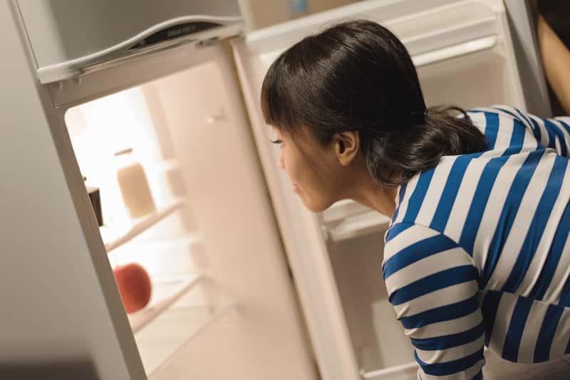 Kobieta zaglądająca do lodówki