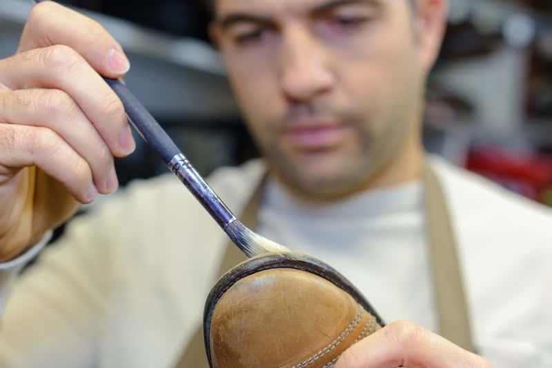Mężczyzna podczas malowania butów