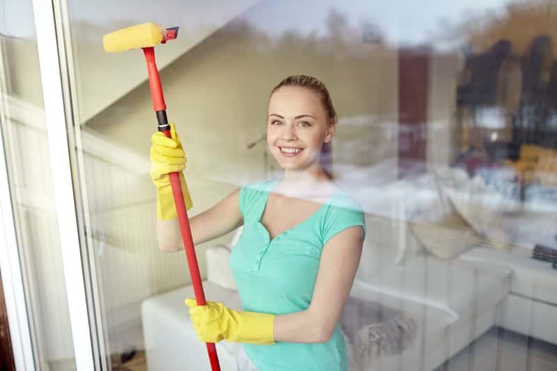 Kobieta podczas mycia okien myjką