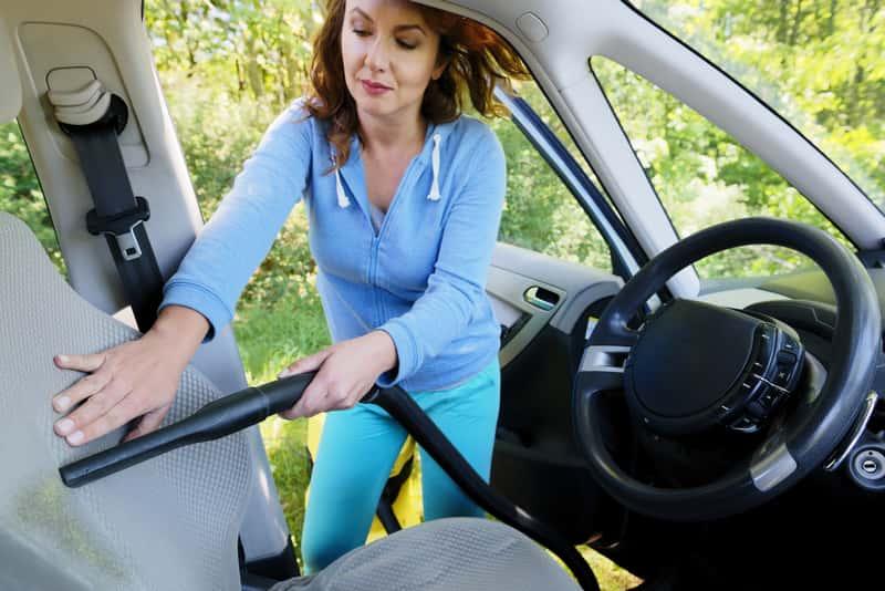 Kobieta odkurzająca samochód