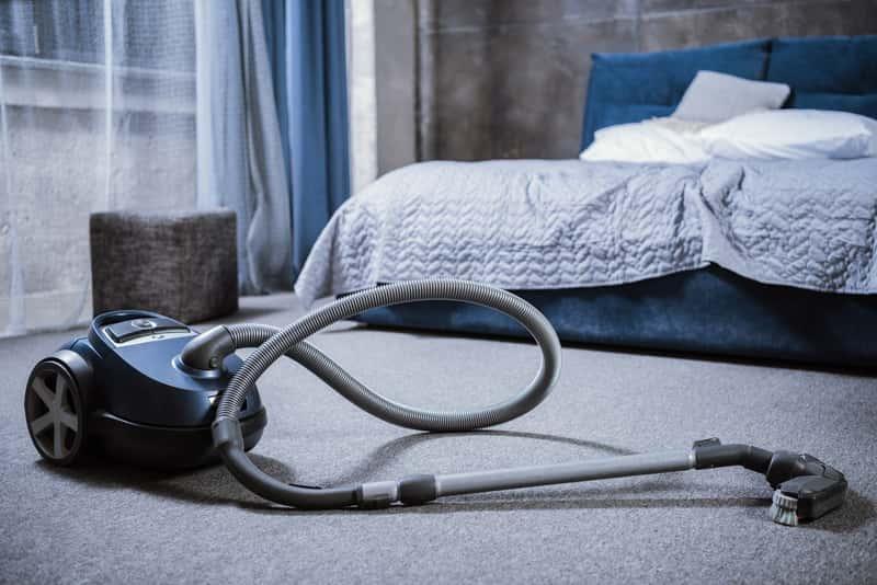 Odkurzacz na dywanie w sypialni