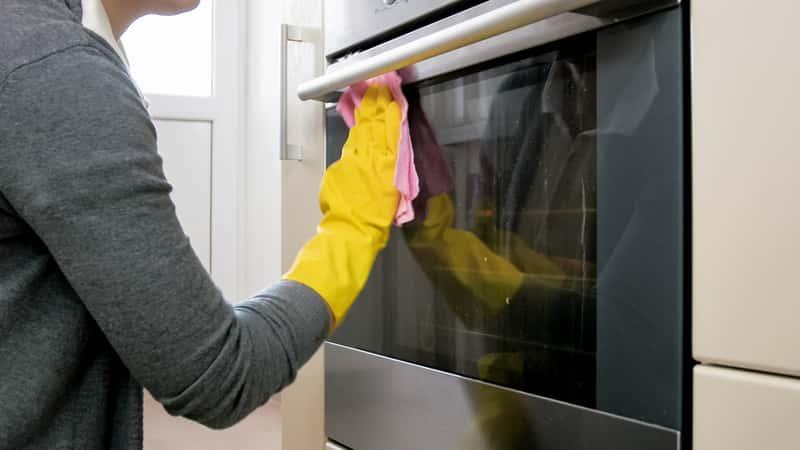 Kobieta myjąca szybę piekarnika