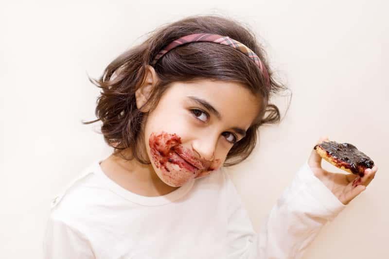 Dziewczynka ubrudzona dżemem z jagód
