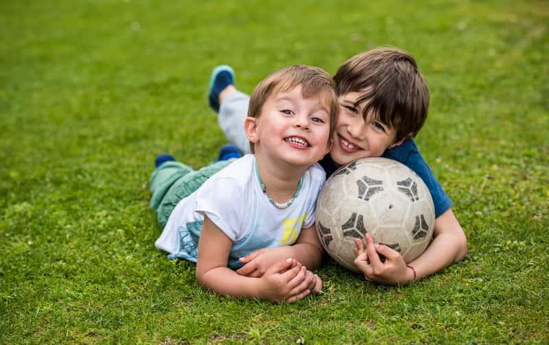 Chłopcy bawiący się na trawie