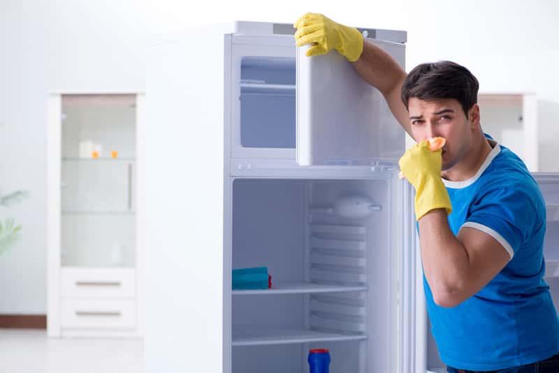 Mężczyzna zatykający nos przy lodówce