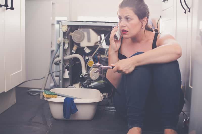 Kobieta przy zepsutej pralce