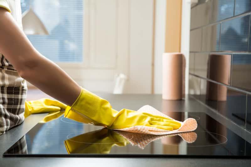 Kobieta czyszcząca płytę kuchenną