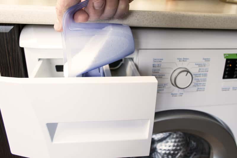 Kobieta wsypująca proszek do pralki
