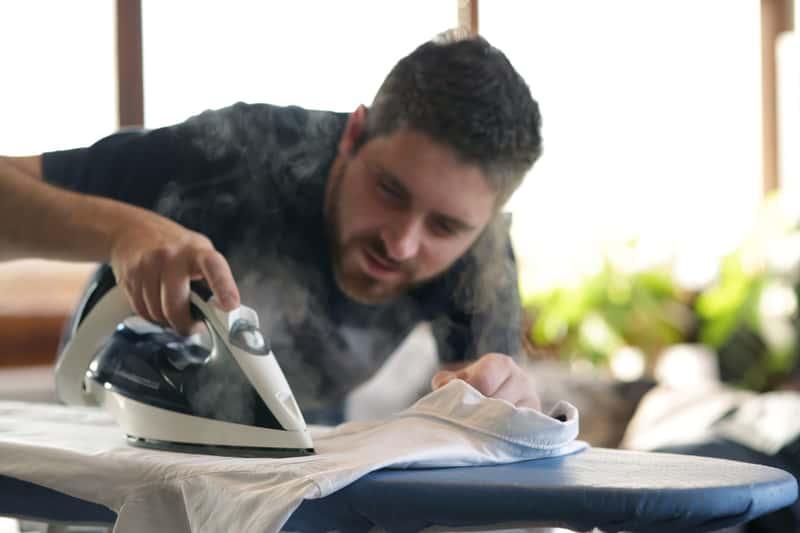 Mężczyzna podczas prasowania ubrań