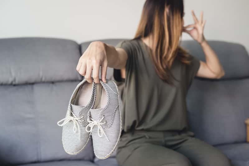 Kobieta z butami zatykająca nos