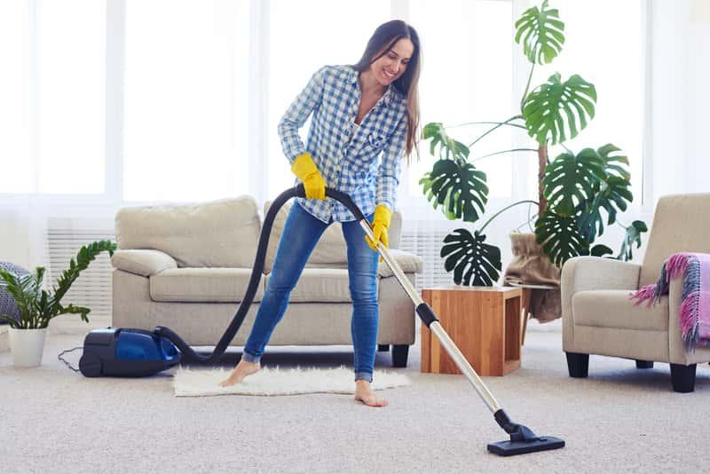 Kobieta podczas odkurzania dywanu