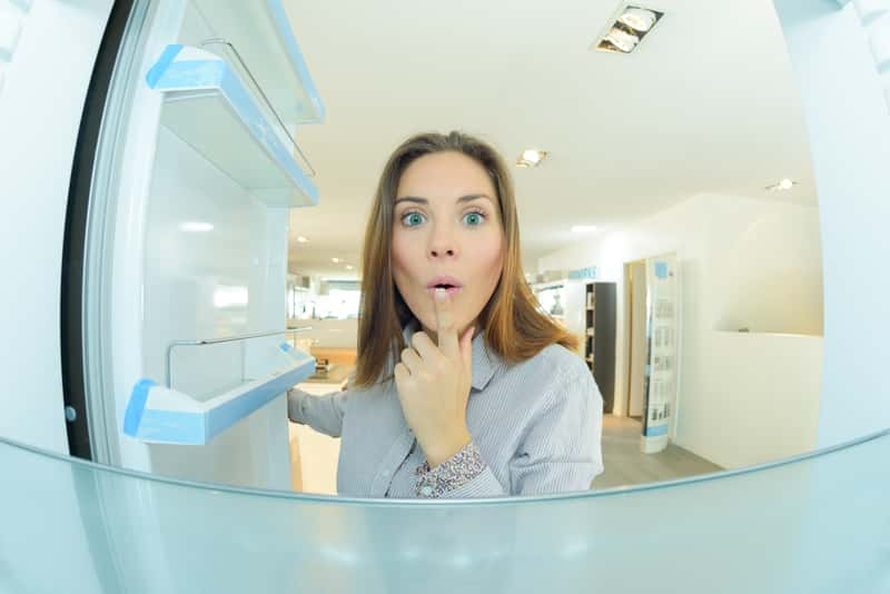 Kobieta zaglądająca do wnętrza lodówki