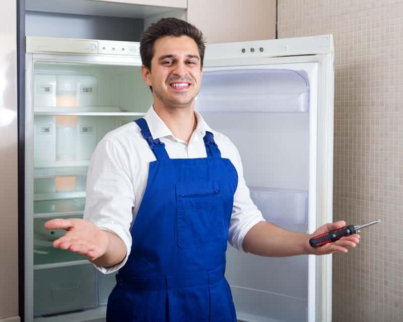 Zadowolony mężczyzna, który dobrze wie, jak wymienić uszczelkę w lodówce