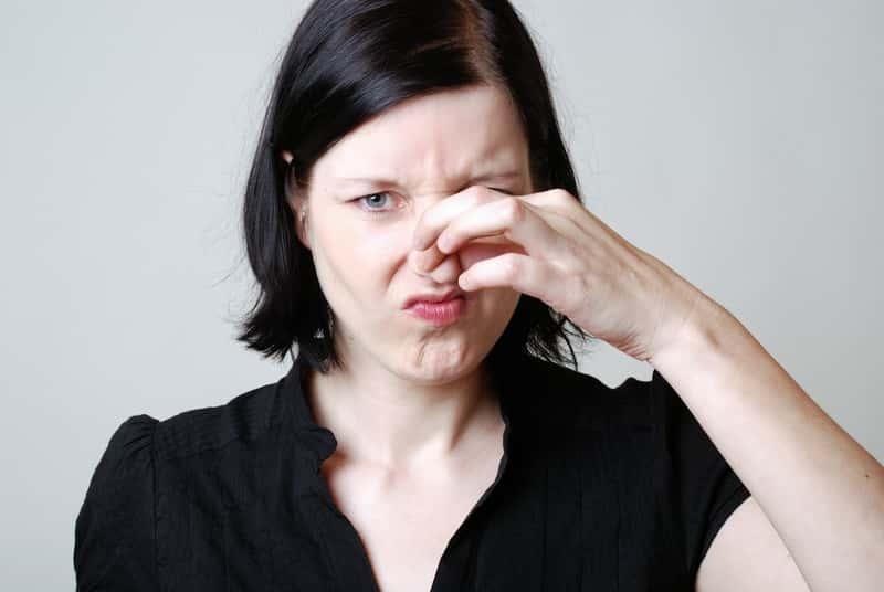 Kobiet zatykająca nos