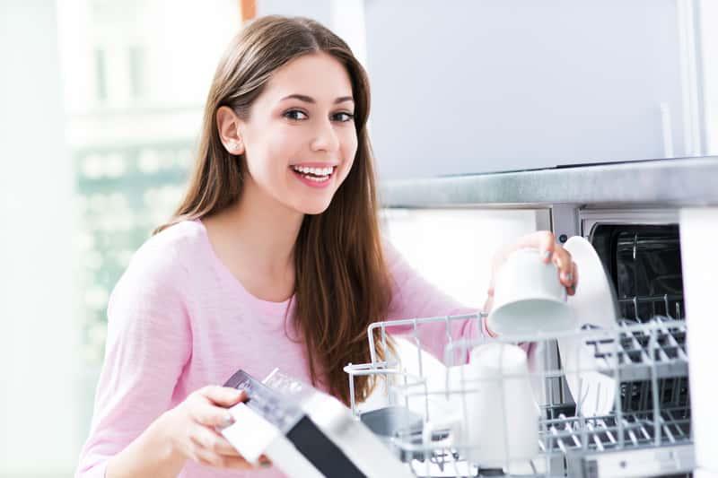 Uśmiechnięta kobieta przy zmywarce