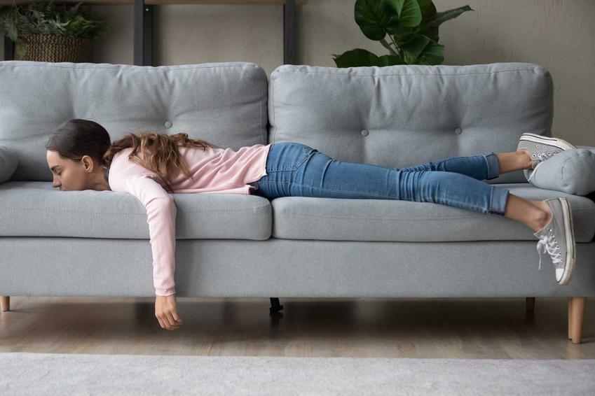 Kobieta na sofie oraz porady, co można robić w domu i sposoby na nudę w domu, a także zabawne pomysły na rozrywkę w domu