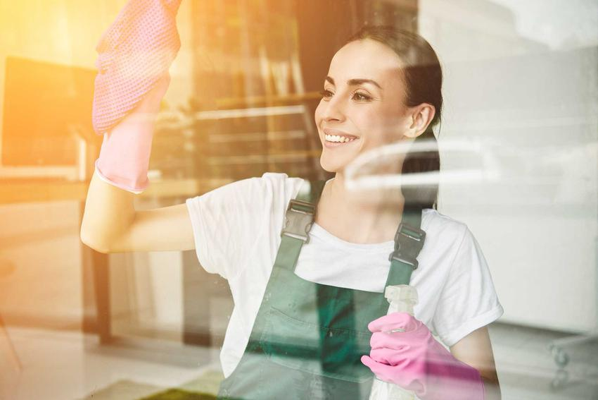 Kobieta poczas mycia okna oraz najlepsze sposoby i porady, jak skutecznie i szybko umyć okna bez smug i zacieków