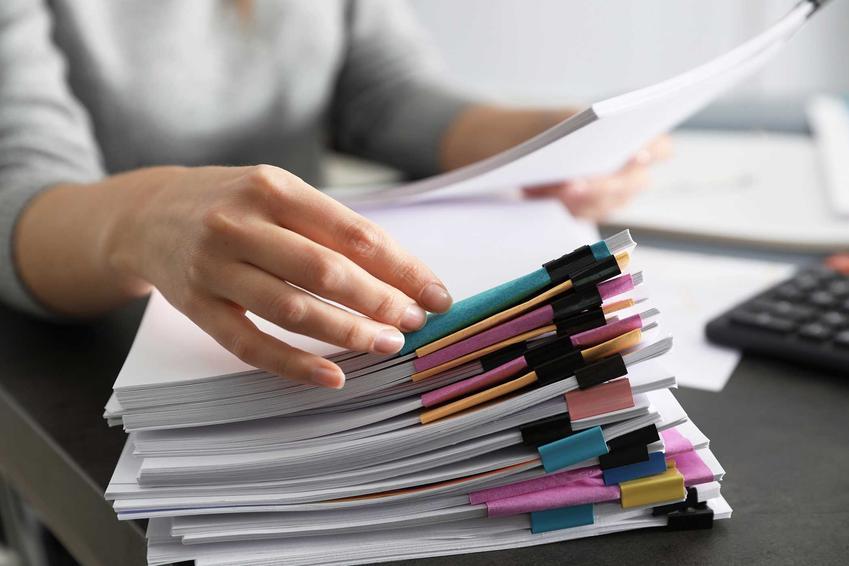 Mężczyzna z dokumentami oraz informacje, jak długo przechowywać dokumenty, ile trzymać rachunki oraz okres przechowywania dokumentów podatkowych