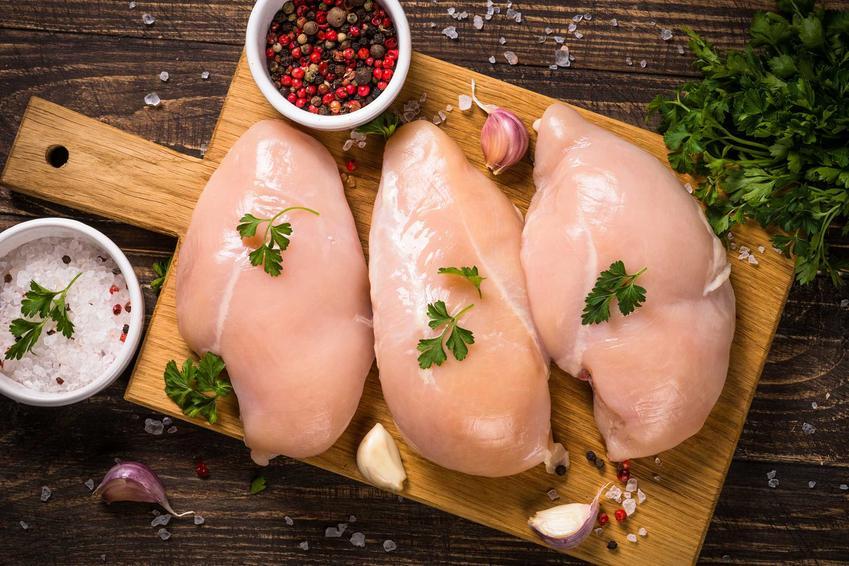 Surowa pierś z kurczaka na desce oraz porady, jak ugotować pierś z kurczaka w wodzie lub w wywarze warzywnym