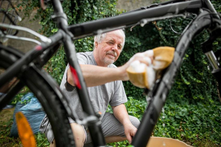 Mężczyzna czyszczący rower, a także porady, jak usunąć rdzę z roweru krok po kroku na stałe za pomocą domowych sposobów