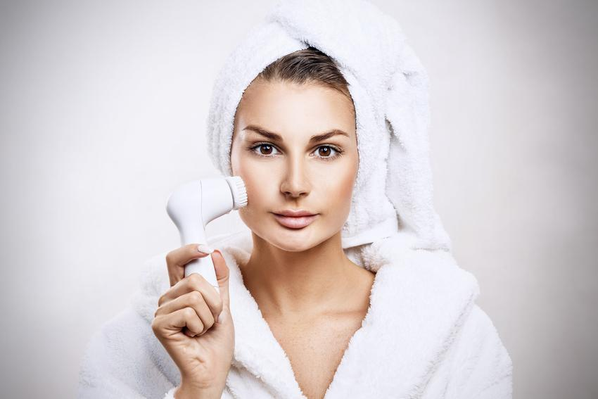 Kobieta myjąca twarz szczoteczką, a także polecana szczoteczka do mycia twarzy