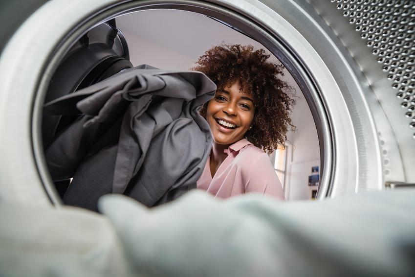 Kobieta zaglądająca do pralki, a także test i ranking suszarek automatycznych