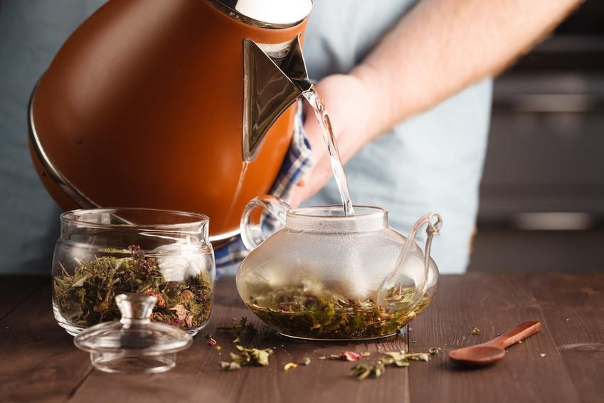 Mężczyzna podczas parzenia herbaty ziołowej, a także porady, jak pozbyć się wody z organizmu