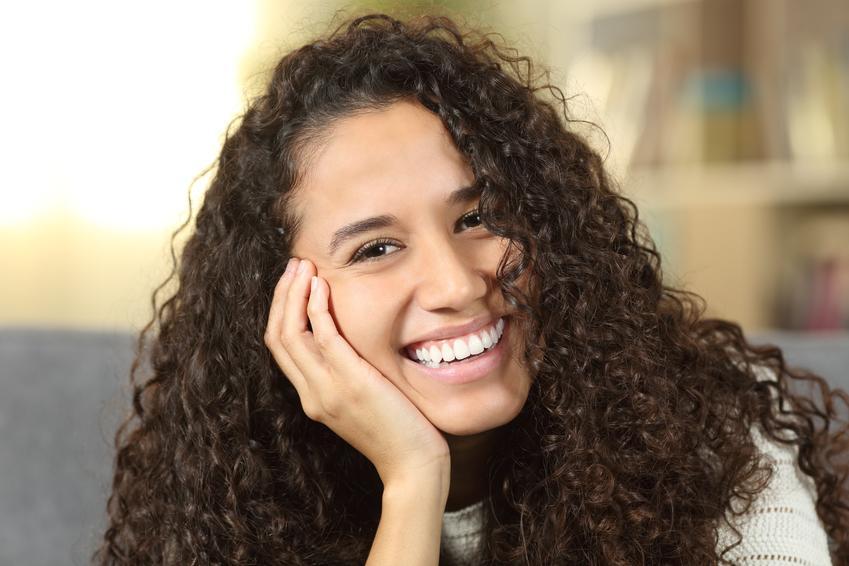 Kobieta z pięknym uśmiechem oraz białymi zębami, a także jak dbać o zęby