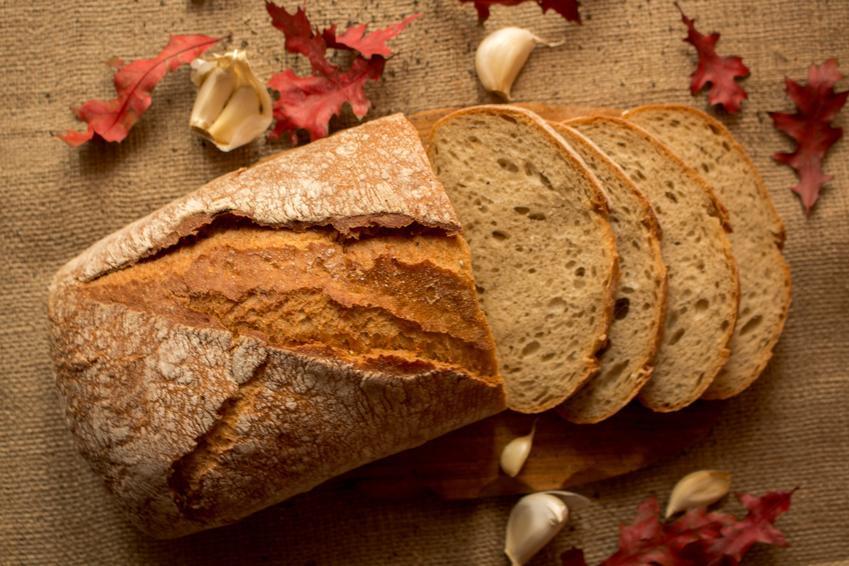 Pokrojony chleb na drewnianej desce oraz domowe sposoby jak odświeżyć chleb