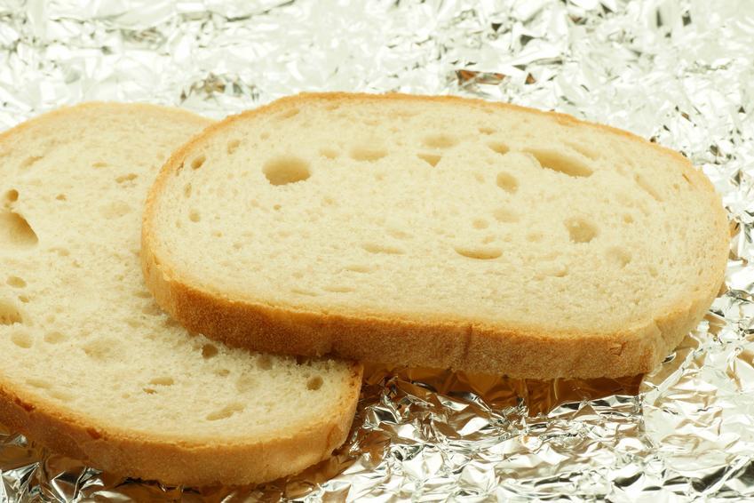 Kromki chleba leżące na folii aluminiowej oraz porady, jak odświeżyć chleb i inne pieczywo