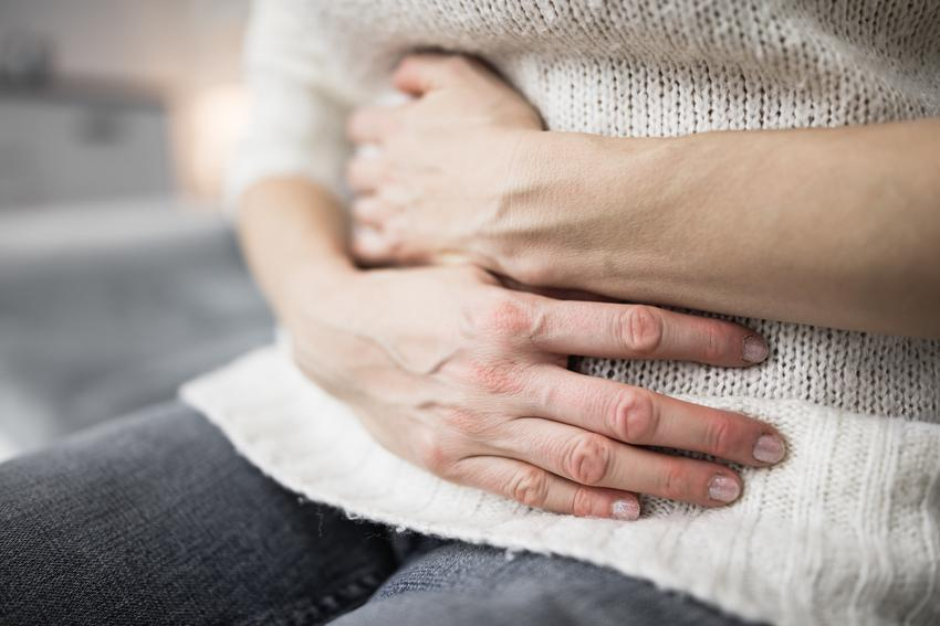 Kobieta trzymająca się za bolący brzuch oraz porady jak się pozbyć tasiemca