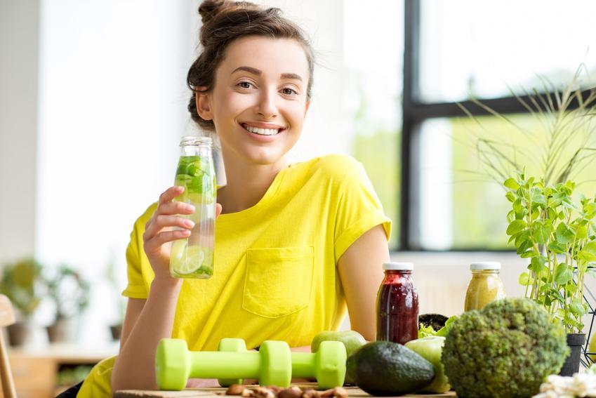 Uśmiechnięta kobieta w zółtej koszulce pijąca wodę z dodatkami i porady, jak oczyścić organizm z toksyn