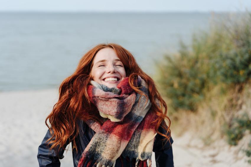 Uśmiechnięta rudowłosa kobieta w szaliku oraz porady, jak wiązać szalik krok po kroku