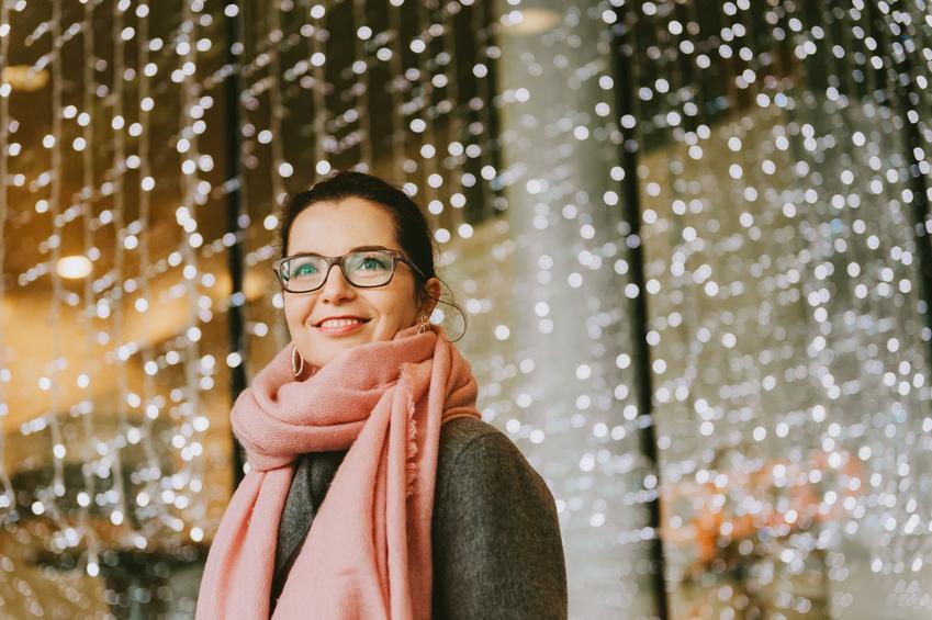 Uśmiechnięta młoda kobieta w różowym szaliku i porady, jak wiązać szalik