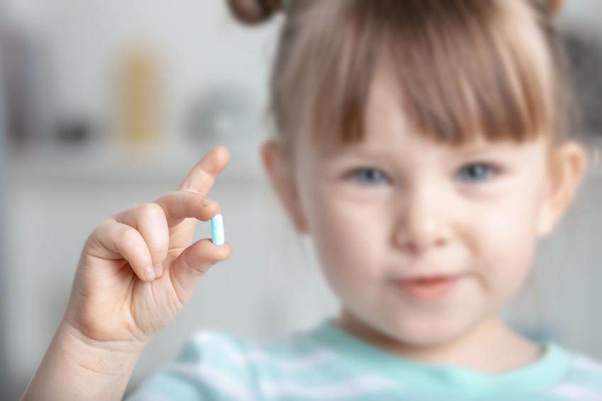 Dziewczynka trzymająca w dłoni lek na odrobaczenie, czyli porady jak odrobaczyć dziecko