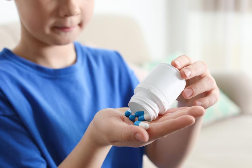 Chłopiec wyjmujący z opakowania lek na odrobaczanie, czyli odrobaczanie dzieci krok po kroku
