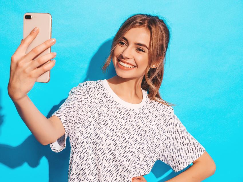 Dziewczyna na niebieskim tle wykonująca pozy do zdjeć typu selfie oraz porady jak pozować do zdjęć