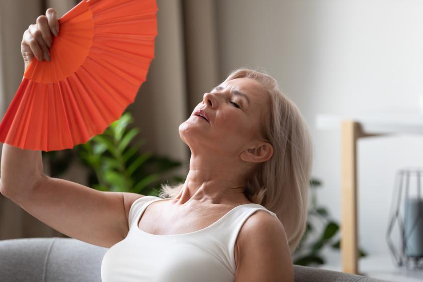 Starsza kobieta wachlująca się wachlarzem oraz w jakim wieku pojawiają się pierwsze objawy menopauzy